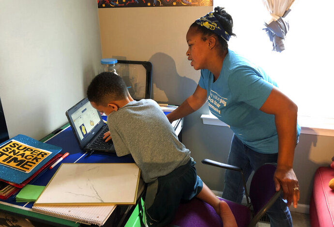 Tiffany Shelton helps her 7-year-old son, P.J. Shelton, a second-grader, during an online class at their home in Norristown, Pa., on Thursday, Sept. 3, 2020. Norristown Area School District plans to offer online-only instruction through at least January 2021. (AP Photo/Michael Rubinkam)
