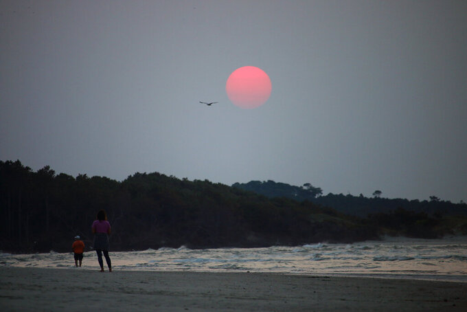A couple walks along the beach in Cherry Grove, S.C., early Thursday, July 22, 2021. Smoke from wildfires in the western U.S. and Canada is blanketing much of the continent, including thousands of miles away on the East Coast. And experts say the phenomenon is becoming more common as human-caused global warming stokes bigger and more intense blazes.  (Mark Rogers/The Sanford Herald via AP)