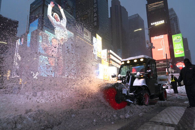 A tractor with a power brush clears snow, Thursday, Dec. 17, 2020, in New York's Times Square. (AP Photo/Mark Lennihan)