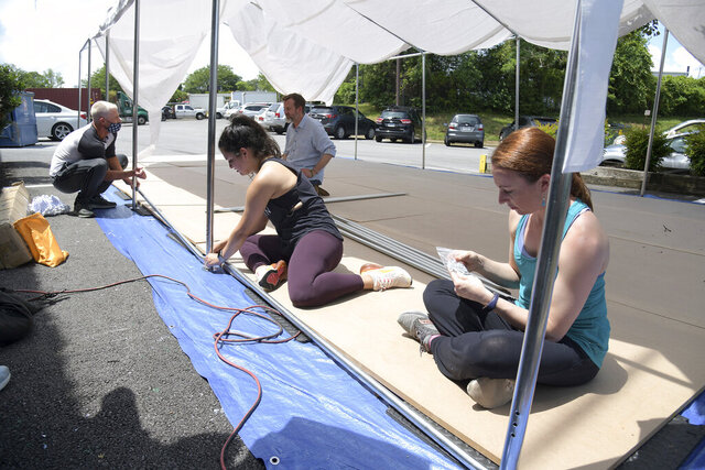 From left, principal dancers Mark McCormack, Emily Brennan, board president Edward Atsinger and Artist Director Nicole Kelsch build the tent. The Ballet Theatre of Maryland is building an outdoor studio space to have classes and rehearsals to help mitigate the spread of COVID-19. (Paul W. Gillespie/The Baltimore Sun via AP)