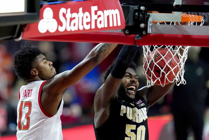 Purdue forward Trevion Williams (50) dunks on Maryland guard Hakim Hart (13) during the first half of an NCAA college basketball game, Tuesday, Feb. 2, 2021, in College Park. (AP Photo/Julio Cortez)
