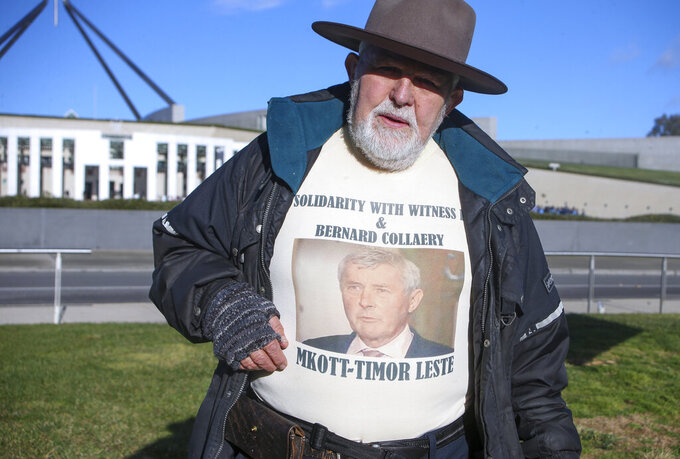 Demonstrator Dierk von Behrens protests outside Parliament House in Canberra, Australia, Thursday, June 17, 2021 against the prosecution of lawyer Bernard Collaery whose picture is on the demonstrator's shirt. Critics of the secret prosecutions of a former Australian spy and his lawyer argue they are another example of a government concealing political embarrassment under the guise of national security. (AP Photo/Rod McGuirk)