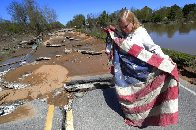 In this Thursday, May 21, 2020 photo, Kim Burgess, the mother of a soldier who was killed in Iraq, holds a muddy American flag after a dam failure destroyed a war memorial last week in Stanford, Mich. Burgess is pledging to rebuild the memorial. (Kirthmon F. Dozier/Detroit Free Press via AP)