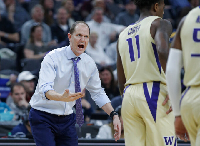 Washington head coach Mike Hopkins speaks with his players during the first half of an NCAA college basketball game against Colorado in the semifinals of the Pac-12 men's tournament Friday, March 15, 2019, in Las Vegas. (AP Photo/John Locher)