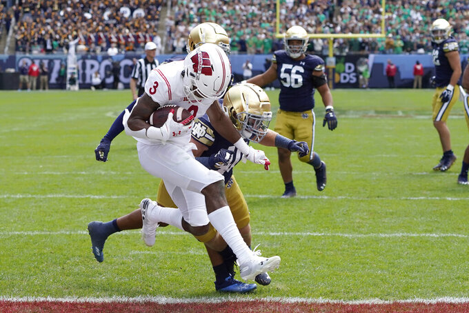 Wisconsin wide receiver Kendric Pryor (3) catches a touchdown pass from quarterback Graham Mertz as Notre Dame linebacker Drew White defends during the second half of an NCAA college football game Saturday, Sept. 25, 2021, in Chicago. Notre Dame won 41-13. (AP Photo/Charles Rex Arbogast)