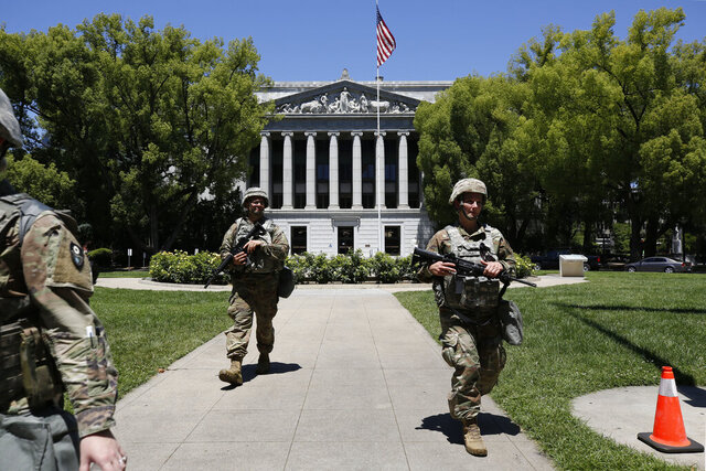 FILE — In this June 2, 2020 file photo members of the California National Guard walk the grounds near the Jesse M. Unruh State Office building in Sacramento, Calif. On Thursday June 11, 2020, California Gov. Gavin Newsom's Administration announced it cost more than $24 million to deploy 8,000 National Guard members for 18 days during the recent protests of racial injustice inspired by the death of Floyd on May 25 in Minneapolis. (AP Photo/Rich Pedroncelli, File)