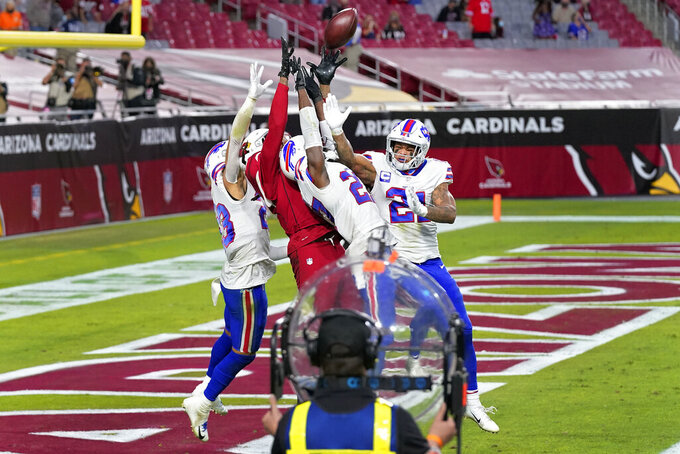 Arizona Cardinals wide receiver DeAndre Hopkins (10) catches the game-winning touchdown as Buffalo Bills cornerback Tre'Davious White, right, free safety Jordan Poyer (21) and strong safety Micah Hyde, left, defend during the second half of an NFL football game, Sunday, Nov. 15, 2020, in Glendale, Ariz. The Cardinals won 32-20. (AP Photo/Ross D. Franklin)