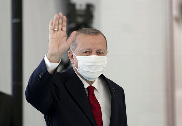 Turkey's President Recep Tayyip Erdogan, wearing a mask for protection against the coronavirus, arrives to inaugurate a new hospital in Istanbul, Friday, May 29, 2020.  Worshippers in Turkey have held their first communal Friday prayers in 74 days after the government reopened some mosques as part of its plans to relax measures in place to fight the coronavirus outbreak. The partial opening of the mosques follows a slowdown in the confirmed COVID-19 infections and deaths in the country. (Can Erok/DHA via AP)