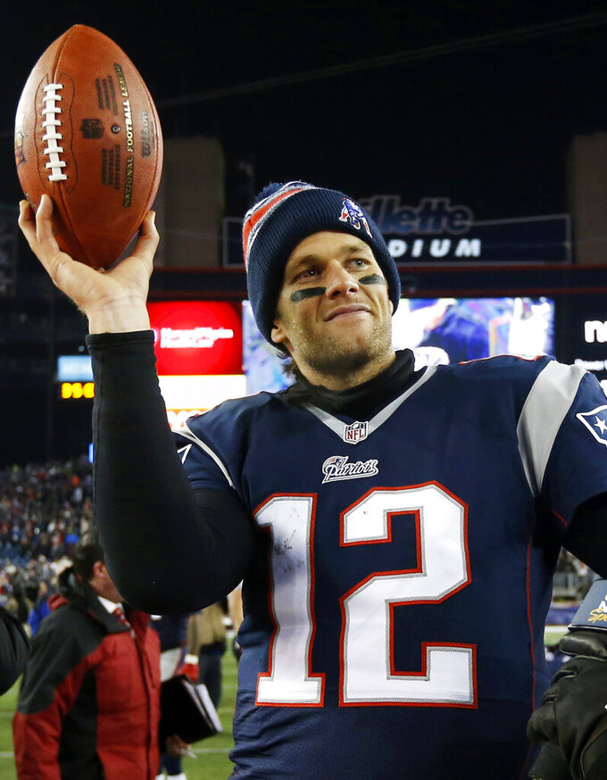 FILE - In this Jan. 10, 2015, file photo, New England Patriots quarterback Tom Brady holds up the game ball after an NFL divisional playoff football game against the Baltimore Ravens in Foxborough, Mass. Brady was selected to the 2010s NFL All-Decade Team announced Monday, April 6, 2020, by the NFL and the Pro Football Hall of Fame. (AP Photo/Elise Amendola, File)
