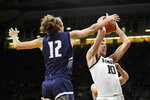 Iowa guard Joe Wieskamp (10) grabs a rebound in front of North Florida guard Ryan Burkhardt, left, during the first half of an NCAA college basketball game, Thursday, Nov. 21, 2019, in Iowa City, Iowa. (AP Photo/Charlie Neibergall)