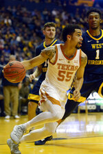 Texas guard Elijah Mitrou-Long (55) maneuvers during the first half of an NCAA college basketball game against West Virginia in Morgantown, W.Va., Saturday, Feb. 9, 2019. (AP Photo/Craig Hudson)