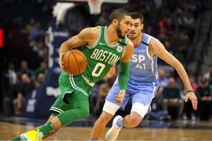 Boston Celtics guard Jayson Tatum (0) drives against Minnesota Timberwolves forward Juancho Hernangomez (41) in the first quarter of an NBA basketball game Friday, Feb. 21, 2020, in Minneapolis. (AP Photo/Andy Clayton-King)