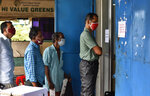 People wearing masks line up to update their details for Aadhar, a government identity card during extended lockdown in Kochi, southern Kerala state, India, Monday, May 18, 2020. India on Monday saw a slow trickle of people returning outdoors and thin traffic on its roads in some states, a day after the federal government extended the nationwide coronavirus lockdown to May 31 but eased many restrictions to restore economic activity. (AP Photo/R S Iyer)