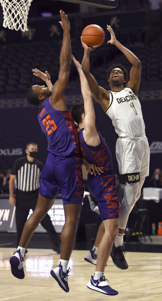 Wake Forest's Isaiah Mucius is fouled by Clemson's Alex Hemenway, center, and pressured by Aamir Simms, left, during an NCAA college basketball game Wednesday, Feb. 24, 2021, in Winston-Salem, N.C. (Walt Unks/The Winston-Salem Journal via AP, Pool)