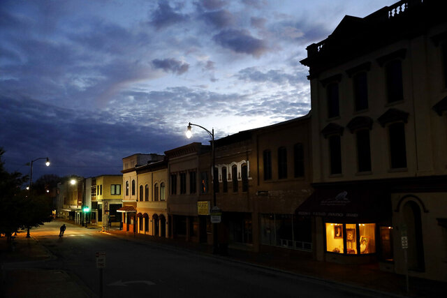 FILE - In this Oct. 28, 2017, file photo the storefront window of a portrait studio is lit up along a downtown street at dusk in Lumberton, N.C. The Community Reinvestment Act has over past four decades spurred hundreds of billions of dollars in lending to low- and middle-income communities. Now, the Trump administration is proposing changes that some community advocates say will make it easier for banks to meet the law's criteria without making the types of loans that are most beneficial to the communities they serve. (AP Photo/David Goldman, File)