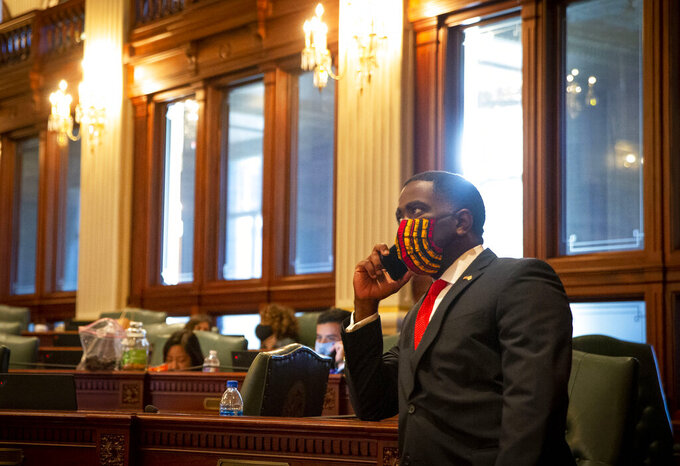 Rep. Marcus Evans, Jr., D-Chicago, talks on the phone prior to session starting on the floor of the Illinois House of Representatives at the Illinois State Capitol in Springfield, Ill., Thursday, Sept. 9, 2021. The Illinois House is poised to approve a wide-ranging plan to eliminate carbon emissions by 2050. A vote planned for Thursday includes a compromise allowing to coal-fired plants to remain open until 2045 but cut their emissions by nearly half in the next 14 years. (Justin L. Fowler/The State Journal-Register via AP)