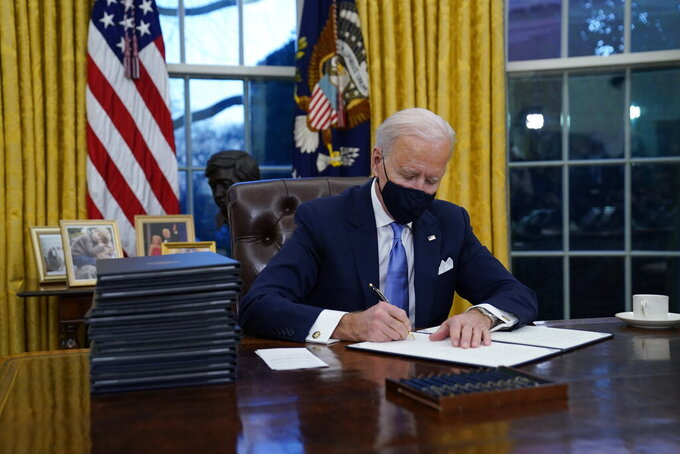 President Joe Biden signs his first executive orders in the Oval Office of the White House on Wednesday, Jan. 20, 2021, in Washington. (AP Photo/Evan Vucci)