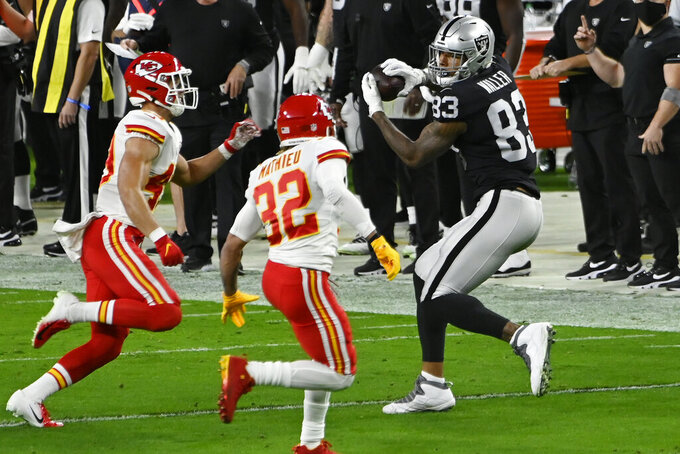 Las Vegas Raiders tight end Darren Waller (83) makes a catch against Kansas City Chiefs strong safety Tyrann Mathieu (32) during the first half of an NFL football game, Sunday, Nov. 22, 2020, in Las Vegas. (AP Photo/David Becker)