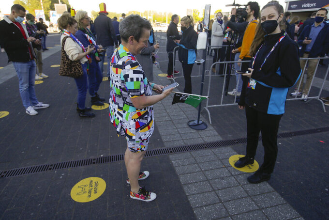 A woman wearing a garment with a TV test card pattern shows her electronic ticket to to hostess as she queues for admission to the first semifinal of the Eurovision Song Contest at Ahoy arena in Rotterdam, Netherlands, Tuesday, May 18, 2021.The competition featuring 39 national songs from nations across Europe as well as Australia and Israel is one of the largest events staged in Europe since the global pandemic began and comes as the continent begins to tentatively ease coronavirus lockdown measures. A crowd of 3,500, tested ahead of time, will be allowed into the Ahoy arena. The number represents a fraction of its capacity to watch the performances live. (AP Photo/Peter Dejong)