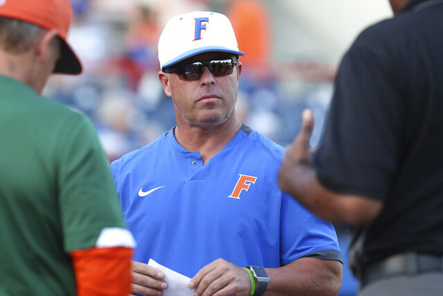 FILE - In this March 4, 2020, file photo, Florida coach Kevin O'Sullivan meets with umpires before the team's NCAA college baseball game against Florida A&M in Gainesville, Fla. The top-ranked Gators are off to a program-record 16-0 start and the only unbeaten team in Division I. (AP Photo/Gary McCullough, File)