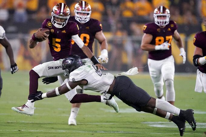 Arizona State quarterback Jayden Daniels (5) avoids the tackle of UNLV linebacker Jacoby Windmon (4) during the second half of an NCAA college football game, Saturday, Sept. 11, 2021, in Tempe, Ariz. (AP Photo/Matt York)