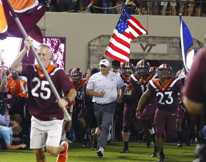 Virginia Tech coach Justin Fuentes, center, runs out with his team before an NCAA college football game against Notre Dame in Blacksburg, Va., Saturday, Oct. 6, 2018. (AP Photo/Steve Helber)