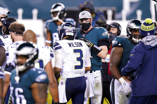 Philadelphia Eagles' Carson Wentz, right, and Seattle Seahawks' Russell Wilson meet after an NFL football game, Monday, Nov. 30, 2020, in Philadelphia. (AP Photo/Chris Szagola)