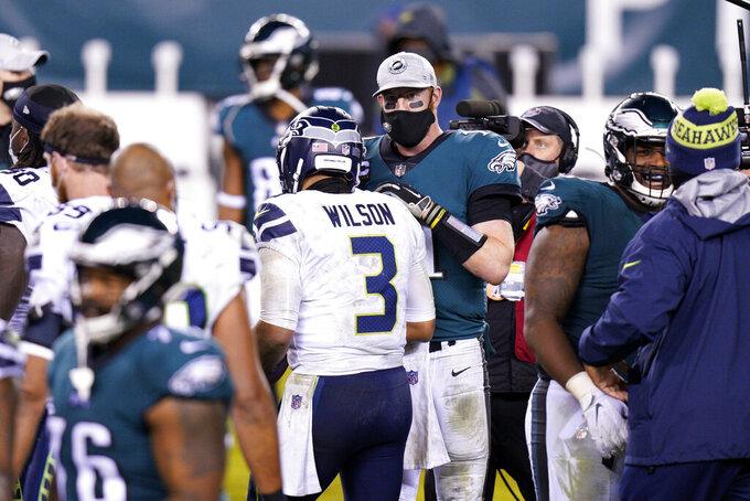 Philadelphia Eagles' Carson Wentz, right, and Seattle Seahawks' Russell Wilson meet after an NFL football game, Monday, Nov. 30, 2020, in Philadelphia. (AP Photo/Chris Szagola)
