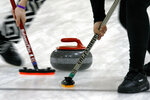 Members of the Colgate curling club sweep ahead of the rock during the college curling national championship, Friday, March 8, 2019, in Wayland, Mass. (AP Photo/Bill Sikes)