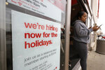 In this Nov. 27, 2019 photo a passer-by walks past a hiring for the holidays sign near an entrance to a Target store location, in Westwood, Mass. On Wednesday, Dec. 4, payroll processor ADP reports on how many jobs its survey estimates U.S. companies added in November. (AP Photo/Steven Senne)