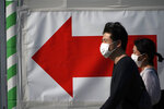 A man and a woman walks near a train station in Tokyo Thursday, April 30, 2020. Japan's Prime Minister Shinzo Abe expanded a state of emergency to all of Japan from just Tokyo and other urban areas as the virus continues to spread. (AP Photo/Eugene Hoshiko)