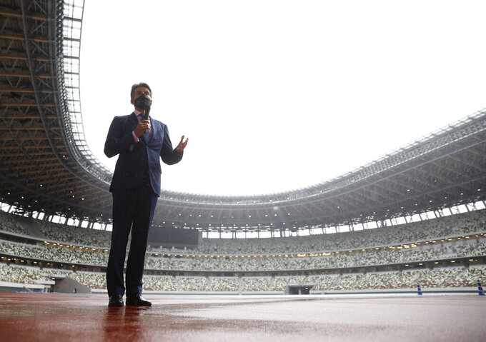 World Athletics President Sebastian Coe wearing a protective face mask speaks to media as he inspects at the National Stadium, the main stadium of Tokyo 2020 Olympics and Paralympics, in Tokyo Thursday, Oct. 8, 2020. (Issei Kato/Pool Photo via AP)