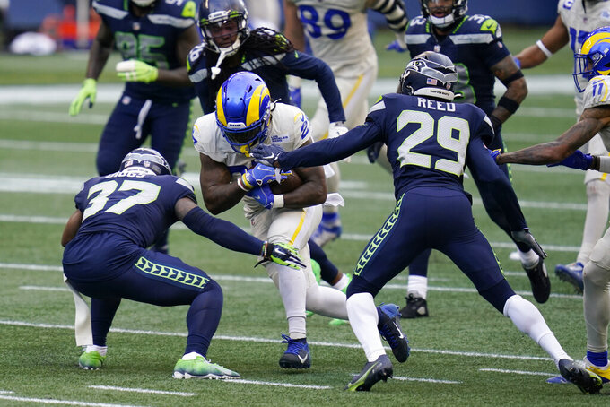 Los Angeles Rams running back Darrell Henderson Jr. (27), center, rushes as Seattle Seahawks free safety D.J. Reed (29) and free safety Quandre Diggs (37) move in for the tackle during the first half of an NFL football game, Sunday, Dec. 27, 2020, in Seattle. (AP Photo/Elaine Thompson)
