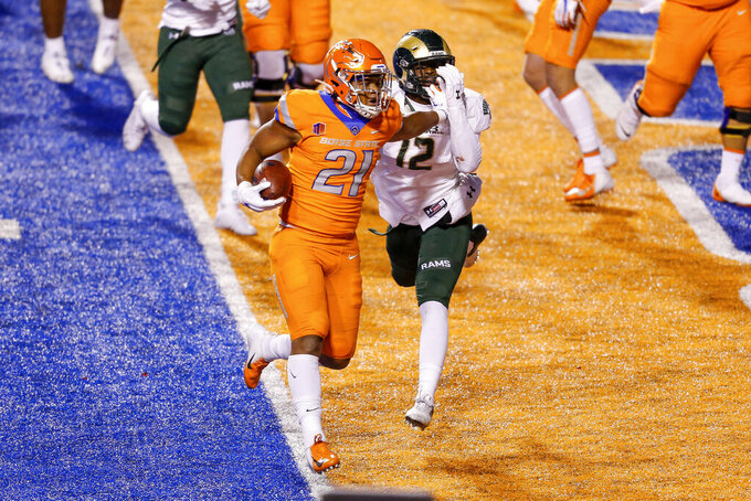 Boise State running back Andrew Van Buren (21) fends off Colorado State linebacker Cam'ron Carter (12) on a 1-yard touchdown during the first half of an NCAA college football game Thursday, Nov. 12, 2020, in Boise, Idaho. (AP Photo/Steve Conner)