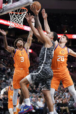 San Antonio Spurs' Trey Lyles, center, attempts to shoot against Phoenix Suns' Kelly Oubre, Jr. (3) and Dario Saric during the first half of an NBA basketball game, Friday, Jan. 24, 2020, in San Antonio. (AP Photo/Darren Abate)