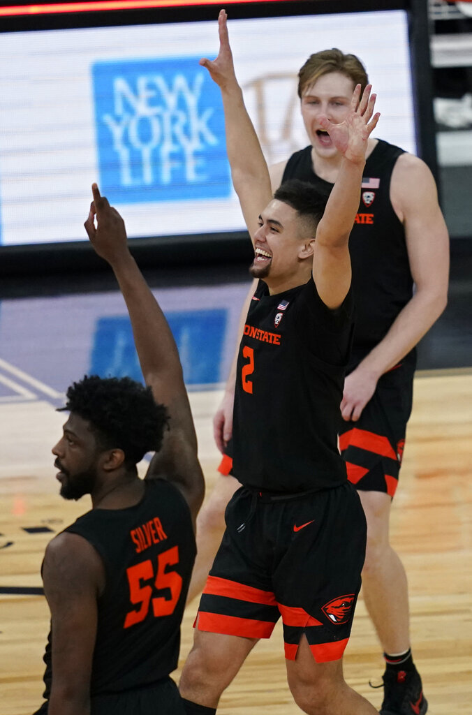 Oregon State's Tariq Silver (55), Jarod Lucas (2) and Zach Reichle celebrate after defeating UCLA in an NCAA college basketball game in the quarterfinal round of the Pac-12 men's tournament Thursday, March 11, 2021, in Las Vegas. (AP Photo/John Locher)