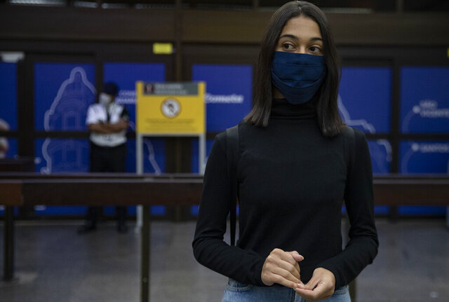 Sara stands at the Guarulhos airport near Sao Paulo, Brazil, a nation where abortion is illegal, waiting for her connecting flight to Buenos Aires, Argentina, where she is traveling to undergo the procedure, Saturday, Dec. 12, 2020. Brazilian women without means have started seeking abortions elsewhere in Latin America to dodge risks and legal obstacles in the region's most populous country. (AP Photo/Andre Penner)