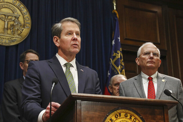 Georgia Gov. Brian Kemp, left, and State Department of Agriculture Commissioner Gary Black, announces that federal disaster relief is on its way to farmers who suffered losses after Hurricane Michael, at the Georgia State Capitol, Wednesday, Feb. 26, 2020 in Atlanta. (Riley Bunch/The Daily Times via AP)
