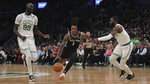San Antonio Spurs guard Lonnie Walker IV (1) drives between Boston Celtics center Tacko Fall (99) and guard Jaylen Brown (7) during the first half of an NBA basketball game Wednesday, Jan. 8, 2020 in Boston. (AP Photo/Charles Krupa)