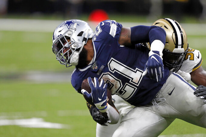 Dallas Cowboys running back Ezekiel Elliott (21) is tackled by New Orleans Saints outside linebacker Demario Davis in the first half of an NFL football game in New Orleans, Sunday, Sept. 29, 2019. (AP Photo/Bill Feig)