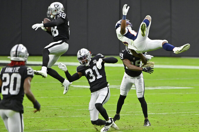 Las Vegas Raiders strong safety Jeff Heath (38) makes an interception on a pass intended for Denver Broncos wide receiver K.J. Hamler, right, during the first half of an NFL football game, Sunday, Nov. 15, 2020, in Las Vegas. (AP Photo/David Becker)