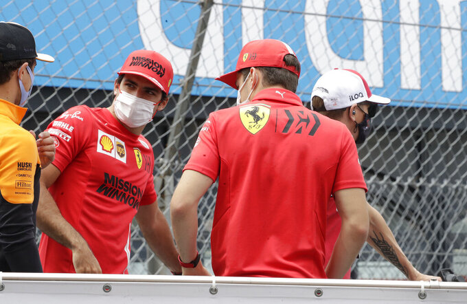 Ferrari driver Carlos Sainz of Spain, second left, speaks with Ferrari driver Charles Leclerc of Monaco, second right, during the drivers parade prior to the Monaco Grand Prix at the Monaco racetrack, in Monaco, Sunday, May 23, 2021. (AP Photo/Luca Bruno)