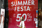 A woman passes by a sale sign at a shopping district in Seoul, South Korea, Thursday, July 18, 2019. South Korea's central bank on Thursday cut its policy rate for the first time in three years to shore up growth threatened by a trade dispute with Japan. (AP Photo/Ahn Young-joon)