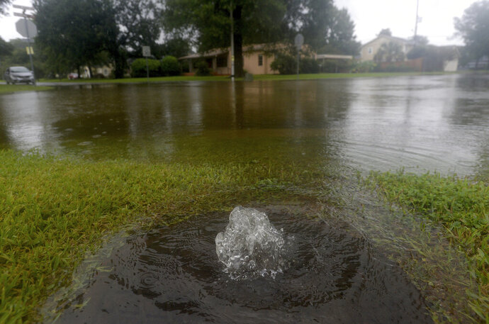 Water bubbles up from a sewer cover at the intersection of Calder Place and 23rd Street in Beaumont where several roads remained heavily flooded throughout the afternoon. Boaters and other emergency personnel were conducting rescue missions to those in need throughout the morning and afternoon, Thursday, September 19, 2019. (Kim Brent/The Beaumont Enterprise via AP)