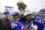 Kentucky players hoist The Governor's Cup after defeating Louisville in the NCAA college football game, Saturday, Nov. 30, 2019, in Lexington, Ky. (AP Photo/Bryan Woolston)
