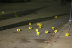 Evidence markers line the street outside a house on Carolina Avenue after a shooting, late Thursday, May 13, 2021, in Providence, R.I. (AP Photo/Stew Milne)