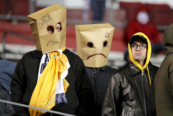 Spectators wear paper bags on their heads while watching the second half of an NCAA college football game between Rutgers and Michigan, Saturday, Nov. 10, 2018, in Piscataway, N.J. (AP Photo/Julio Cortez)