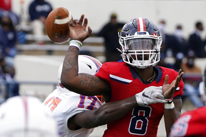 Jackson State quarterback Quincy Casey (8) has the football knocked from his hand as he attempts to pass by Edward Waters linebacker Derrick Nicholson (17) during the second half of an NCAA college football game in Jackson, Miss., Sunday, Feb. 21, 2021. (AP Photo/Rogelio V. Solis)