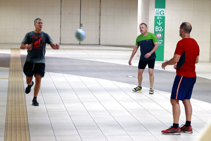 England rugby fans warm up with a rugby ball at an underground pathway in Tokyo Saturday, Oct. 12, 2019. A heavy downpour and strong winds pounded Tokyo and surrounding areas on Saturday as a powerful typhoon forecast as the worst in six decades approached landfall, with streets and train stations deserted and shops shuttered. (AP Photo/Eugene Hoshiko)