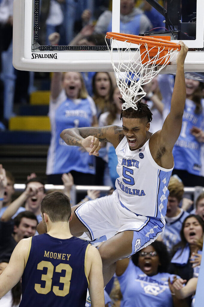 North Carolina forward Armando Bacot (5) reacts following a dunk as Notre Dame forward John Mooney (33) looks on during the second half of an NCAA college basketball game in Chapel Hill, N.C., Wednesday, Nov. 6, 2019. North Carolina won 76-65. (AP Photo/Gerry Broome)